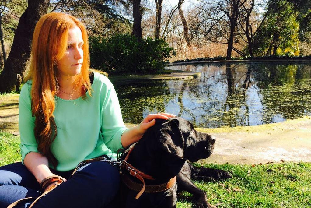 La trabajadora de ILUNION Sara Martínez en un parque junto a su perro guía