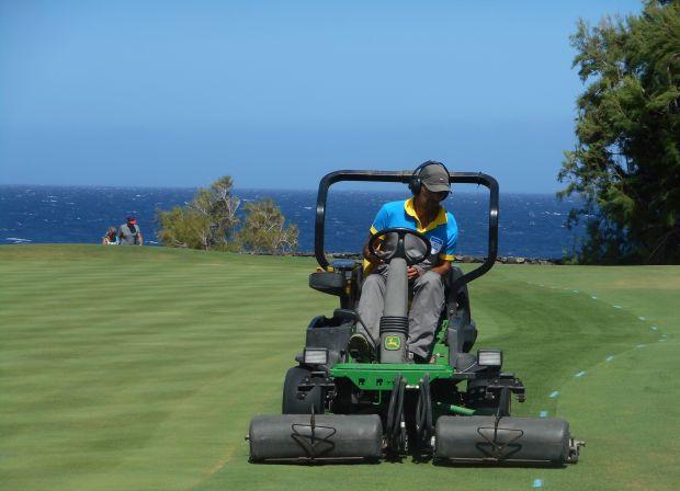 Un cortacesped cortando el cesped en un campo de Golf